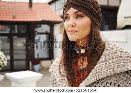Portrait of a young woman dressed in fashion hat and boho style accessories, autumn fashion