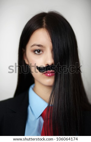 portrait of a young woman dressed up in a man's suit and tie wearing a fake mustache - stock photo