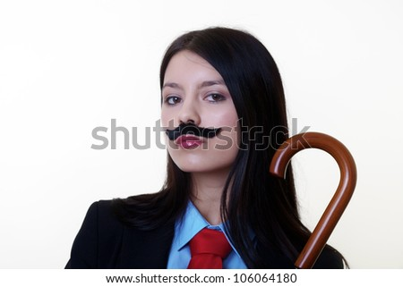 portrait of a young woman dressed up in a man's suit and tie wearing a fake mustache holding a umbrella - stock photo