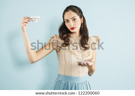 portrait of a young woman drinking a cup of tea, vintage style. - stock photo