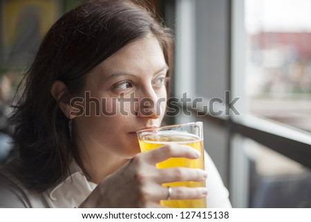 Portrait of a young woman drinking a pint of hard cider. - stock photo