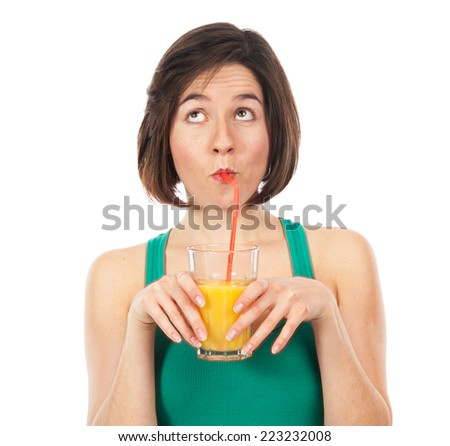Portrait of a young woman drinking an orange juice with a straw, and looking up isolated on white - stock photo
