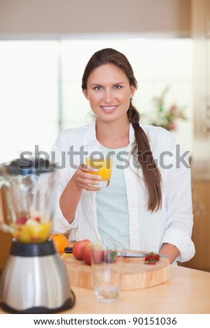 Portrait of a young woman drinking fresh fruits juice in her kitchen - stock photo