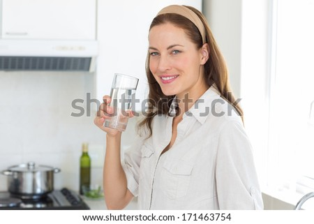 Portrait of a young woman drinking water in the kitchen at home - stock photo