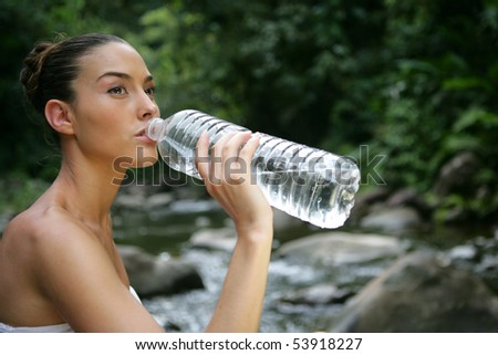 Portrait of a young woman drinking water next to a river