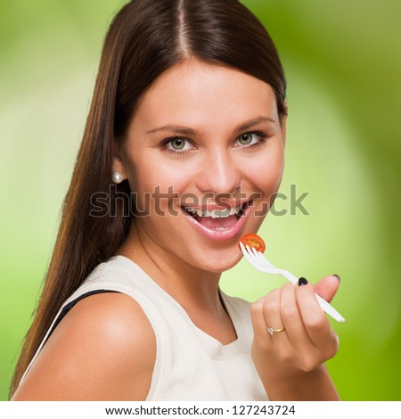 Portrait Of A Young Woman Eating a Salad against a nature background - stock photo