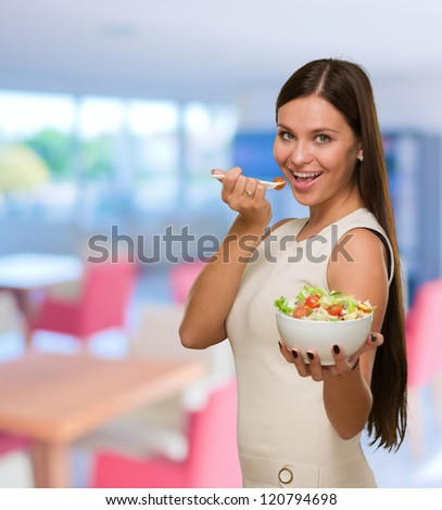 Portrait Of A Young Woman Eating A Salad at a restaurant