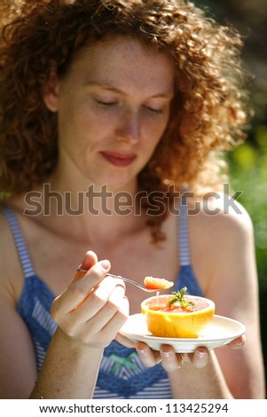 Portrait of a young woman eating an orange outdoors