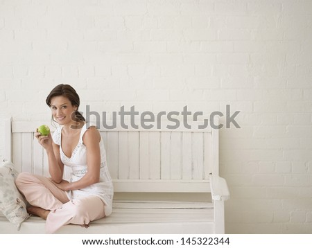 Portrait of a young woman eating apple on bench - stock photo