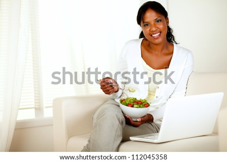 Portrait of a young woman eating healthy salad and looking at you while is sitting on couch in front of her laptop. with copyspace - stock photo