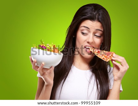 portrait of a young woman eating pizza and looking at a salad over a green background