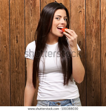 portrait of a young woman eating strawberry against a wooden wall