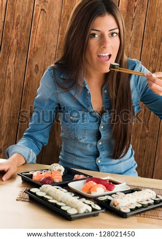 Portrait Of A Young Woman Eating Sushi Maki against a wooden background - stock photo
