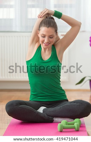 Portrait of a young woman exercising at home. She is sitting cross-legged on the floor and doing stretching exercise with her arms above her head. - stock photo