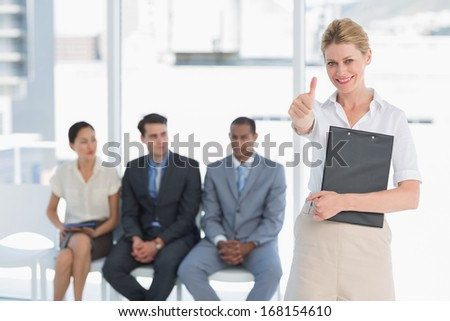 Portrait of a young woman gesturing thumbs up with people waiting for job interview in a bright office - stock photo