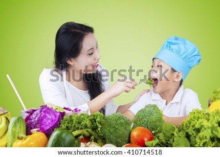 Portrait of a young woman giving fresh vegetables on her son wit a fork, shot with green background - stock photo