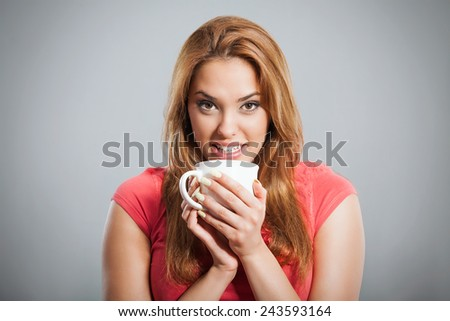 Portrait of a young woman having a cup of hot drink. Studio shot.