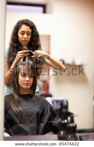 Portrait of a young woman having a haircut looking away from the camera - stock photo