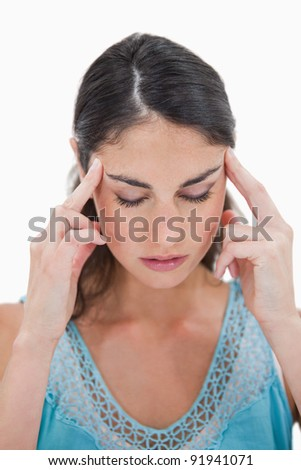 Portrait of a young woman having a headache against a white background
