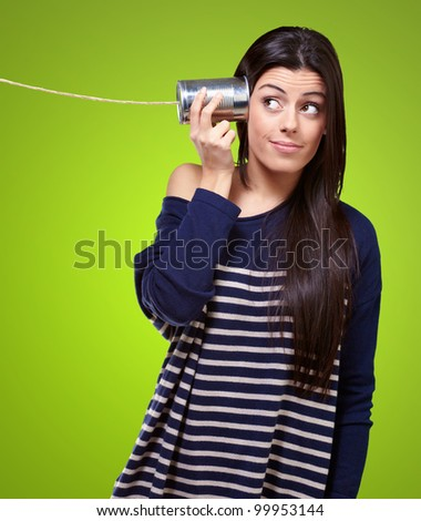 portrait of a young woman hearing through a tin can over a green background - stock photo