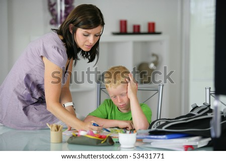 Portrait of a young woman helping a little boy to do homework