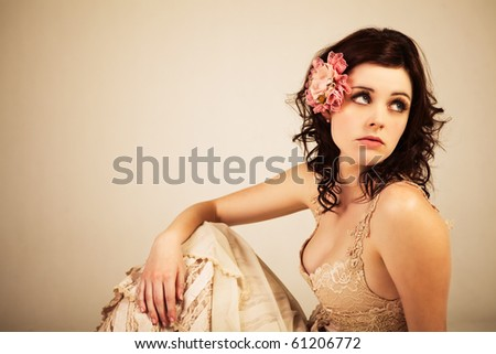 Portrait of a young woman. Her hair is styled with a flower and she is wearing a vintage dress. - stock photo