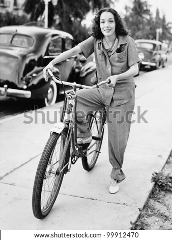 Portrait of a young woman holding a bicycle and smiling - stock photo