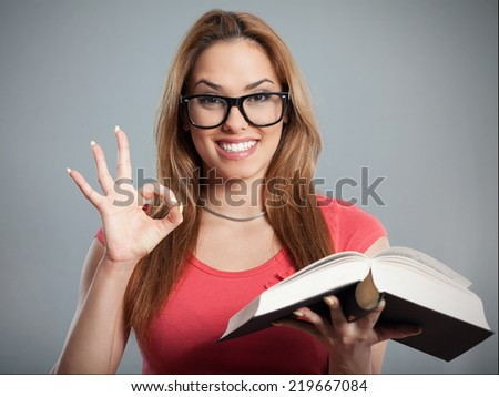 Portrait of a young woman holding a book and showing ok sign - stock photo