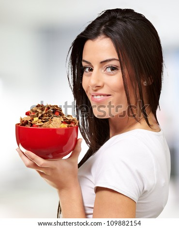 portrait of a young woman holding a bowl of cereals indoor - stock photo