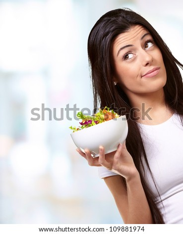 portrait of a young woman holding a bowl of salad indoor
