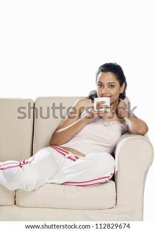 Portrait of a young woman holding a coffee mug - stock photo