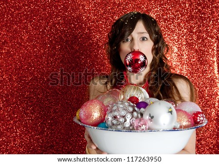Portrait of a young woman holding a dish full of Christmas bar balls with one of them in her mouth, being humorous while standing in front of a red glitter background.