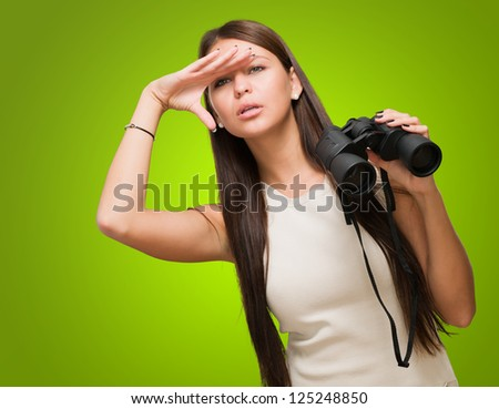 Portrait Of A Young Woman Holding Binoculars And Searching against a green background - stock photo