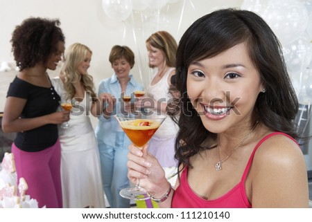 Portrait of a young woman holding cocktail glass with friends in the background - stock photo