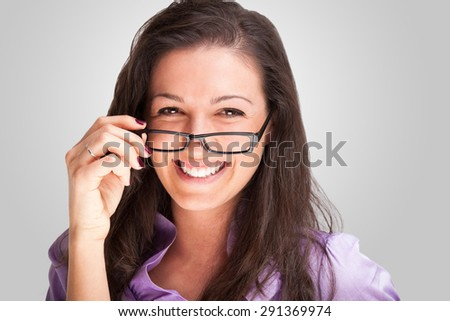 Portrait of a young woman holding her eyeglasses - stock photo