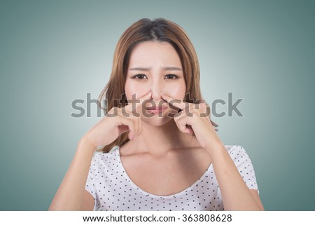 Portrait of a young woman holding her nose because of a bad smell. - stock photo
