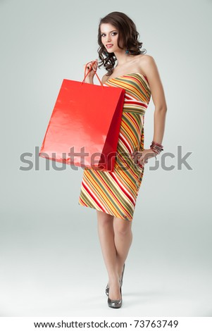 portrait of a young woman holding in one hand a red shopping bag and the other one on her hip. she is laughing and looking very happy.