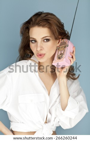 Portrait of a Young woman holding retro radio  - stock photo