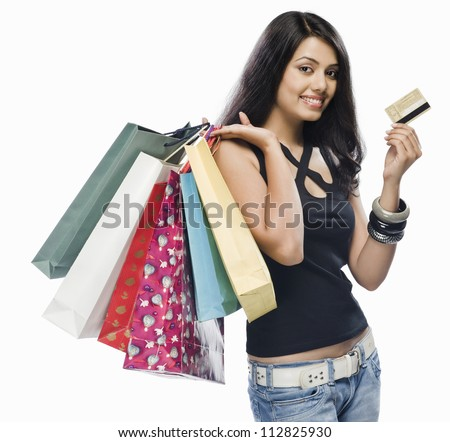 Portrait of a young woman holding shopping bags and a credit card