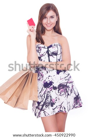 Portrait of a young woman holding shopping bags and a credit card - stock photo