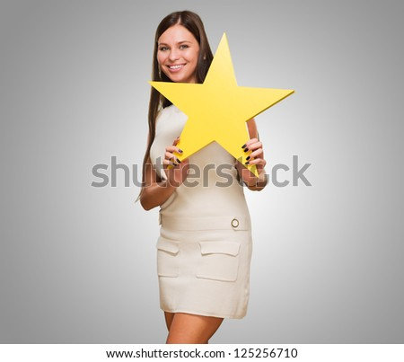 Portrait Of A Young Woman Holding Star against a grey background - stock photo
