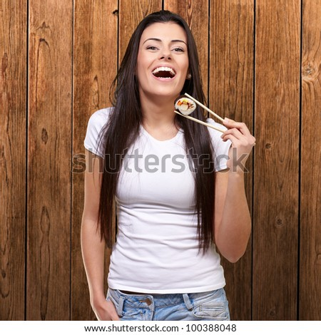 portrait of a young woman holding sushi against a wooden wall