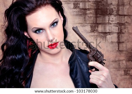 Portrait of a young woman holding the pistol