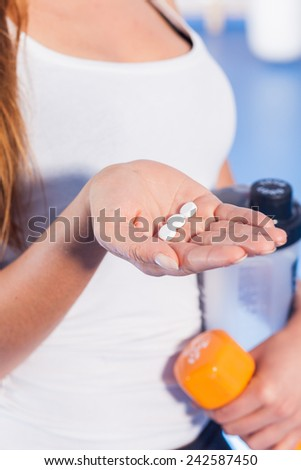 Portrait of a young woman holding weight (dumbbell) and vitamins