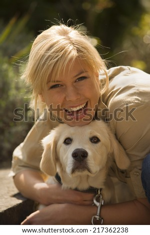 Portrait of a young woman hugging her dog - stock photo