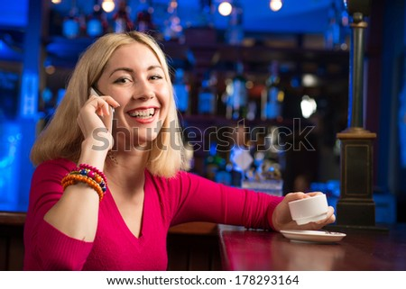 portrait of a young woman in a bar with a cell phone and a cup of coffee