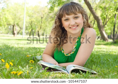 portrait of a young woman in a park reading a magazine
