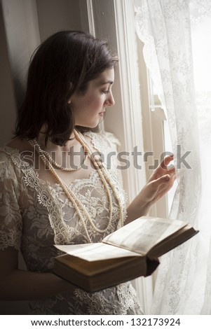 Portrait of a young woman in a vintage white wedding dress reading a book.