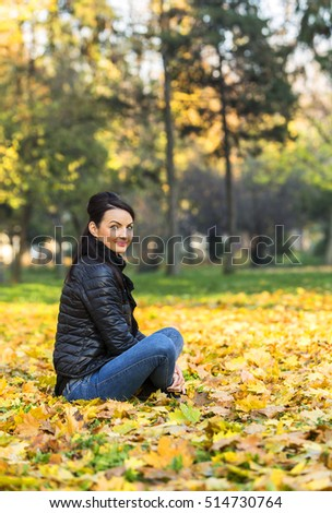 Portrait of a young woman in a yellow autumn forest.