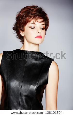 portrait of a young woman in leather dress with red hair wearing short pixie crop hairstyle on studio background  - stock photo